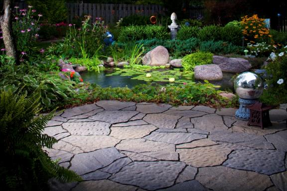 The natural texture of Mega Arbel pavers pair perfectly with this natural oasis.